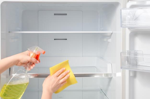 Limpeza doméstica - borrifador com detergente para lavar a geladeira.
