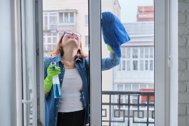 Limpeza doméstica, mulher adulta em luvas com pano de microfibra borrifado com detergente janela de vidro limpa no quarto, espaço de cópia