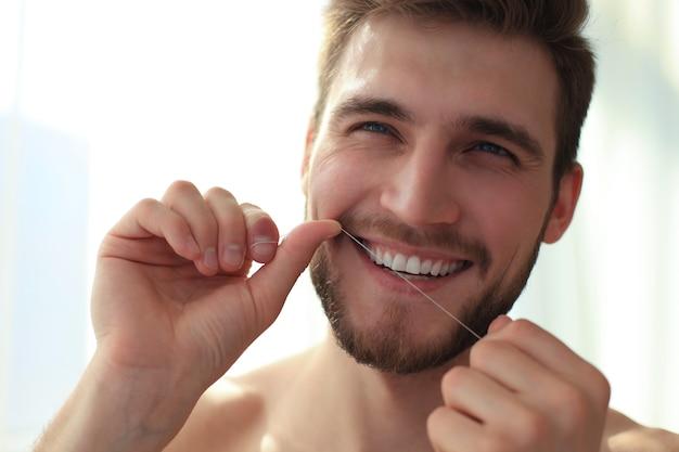 Limpeza dos dentes com fio dental. jovem bonito sem camisa, limpando os dentes com fio dental e sorrindo.