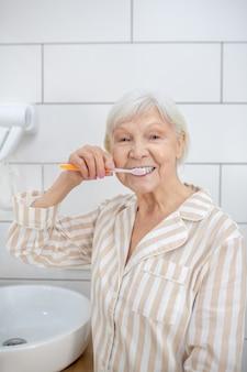 Limpeza dos dentes. mulher idosa de pijama limpando os dentes