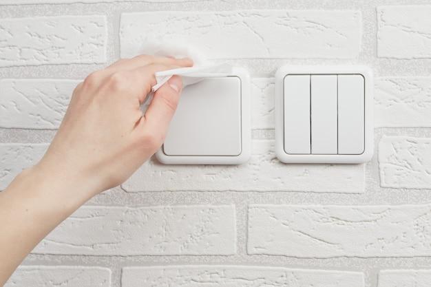 Limpeza e desinfecção de interruptores de luz doméstica de coronavírus durante a pandemia covid-19.