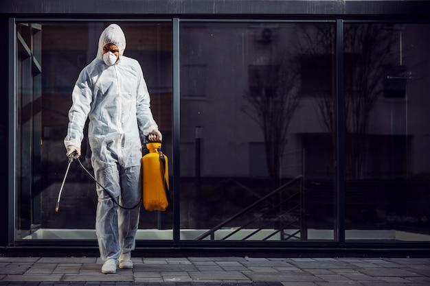 Limpeza e desinfecção do lado de fora em torno dos edifícios, a epidemia covid-19. equipes de sessões para os esforços de desinfecção. prevenção de infecções e controle de epidemia. e terno e máscara.