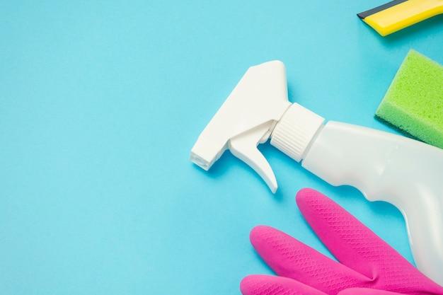 Limpeza e limpeza de acessórios, luvas, spray, esponjas, raspador para janelas em um fundo azul. conceito de serviço de limpeza. copie o espaço. vista plana, vista superior