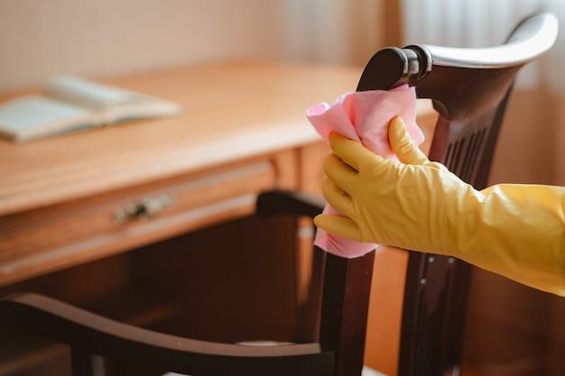 Limpeza e manutenção da mesa da cadeira de madeira com pano e agente de limpeza