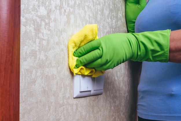 Limpeza em casa. uma garota de luvas verdes limpa o interruptor de eletricidade com um pano amarelo