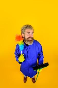Limpeza ferramentas de limpeza escova de poeira limpeza doméstica homem sorridente de uniforme com escova de poeira