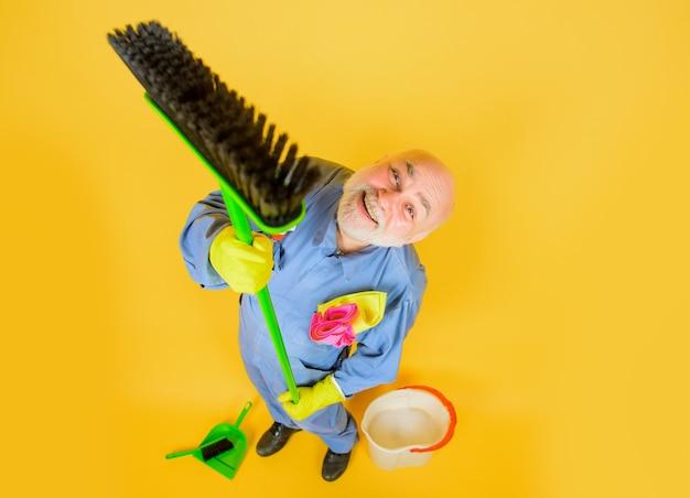 Limpeza ferramentas domésticas homem barbudo de uniforme com vassoura de limpeza profissional de serviço doméstico