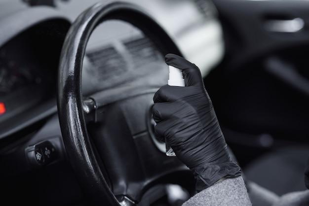 Limpeza interior do carro e pulverização com líquido de desinfecção. mãos na luva protetora de borracha que desinfetam o veículo dentro para proteção contra doenças virais