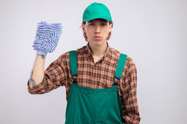 Limpeza jovem com macacão de camisa xadrez e boné segurando o espanador com rosto sério pronto para limpar em pé sobre uma parede branca
