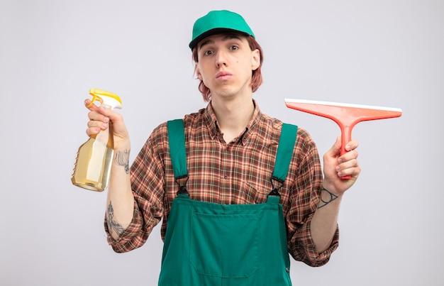 Limpeza jovem com macacão e boné de camisa xadrez segurando spray de limpeza e esfregão com cara séria em pé sobre uma parede branca
