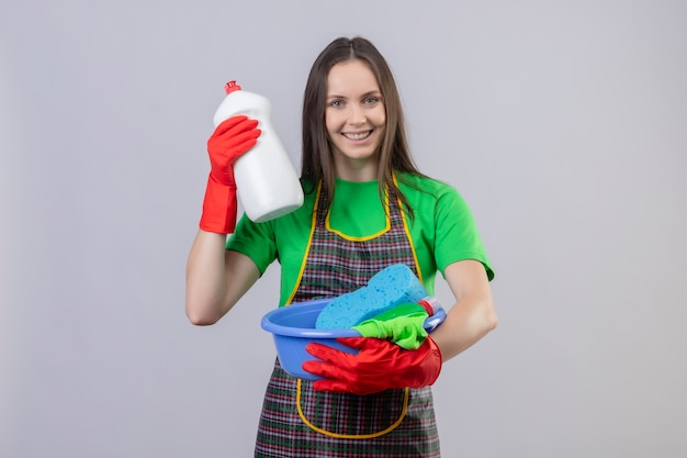 Limpeza jovem sorridente, usando uniforme com luvas vermelhas, segurando ferramentas de limpeza e agente de limpeza no fundo branco isolado