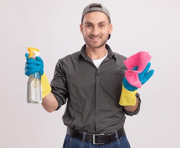 Limpeza jovem vestindo roupas casuais e boné em luvas de borracha segurando um frasco de spray e um pano, parecendo feliz e positivo, sorrindo em pé sobre uma parede branca