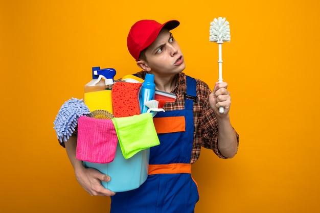 Limpeza jovem vestindo uniforme e boné segurando balde de ferramentas de limpeza e olhando para a escova na mão isolada na parede laranja
