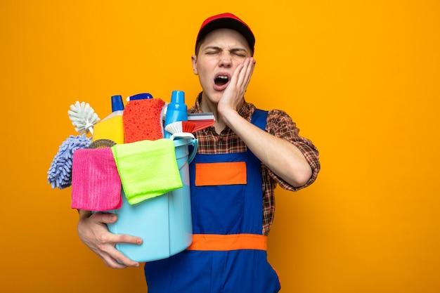 Limpeza jovem vestindo uniforme e boné segurando um balde com ferramentas de limpeza isolado na parede laranja