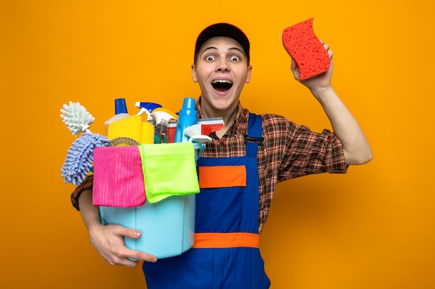 Limpeza jovem vestindo uniforme e boné segurando um balde de ferramentas de limpeza com uma esponja isolada na parede laranja