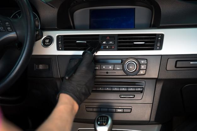 Limpeza manual do interior do automóvel com auxílio de escovagem.