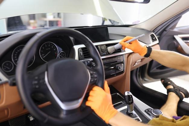 Limpeza manual do interior do carro com escova para locais difíceis de alcançar no painel de controle do carro.