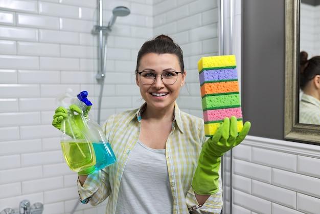 Limpeza no banheiro. mulher limpando o banheiro em casa segurando detergentes e esponjas nas mãos