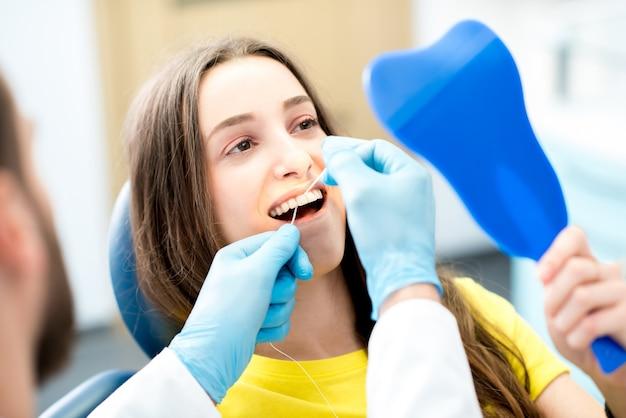 Limpeza profissional dos dentes com fio dental no consultório odontológico
