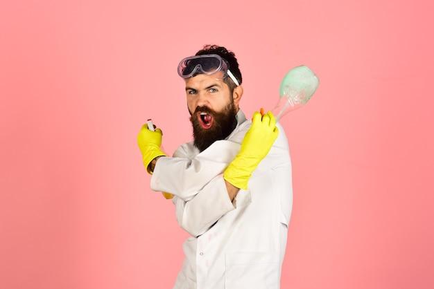 Limpeza, serviço de limpeza, conceito de limpeza - homem barbudo zangado de uniforme e luvas de borracha contém spray de limpeza. meios de limpeza eficazes. copie o espaço para anunciar detergentes, serviço de limpeza.