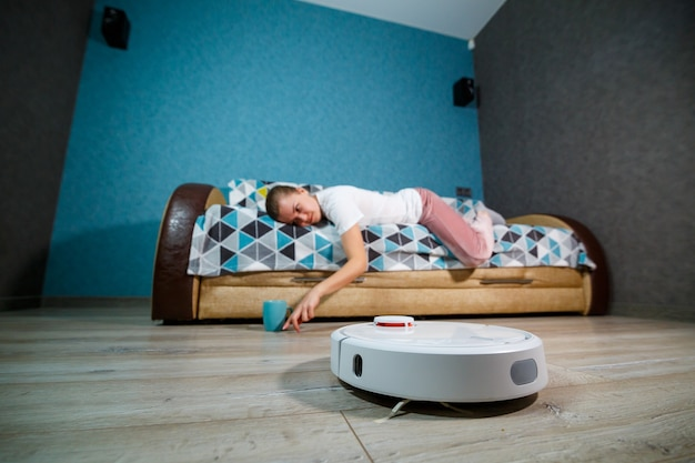 Limpeza simples e fácil com tecnologia moderna para o uso doméstico. menina bebe chá e descansa enquanto o aspirador faz a limpeza da casa