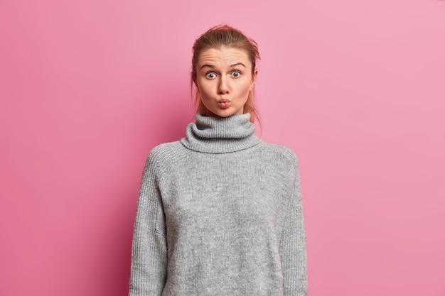 Linda adolescente com cabelo penteado, veste um suéter cinza quente solto, parece surpreendente, mantém os lábios arredondados