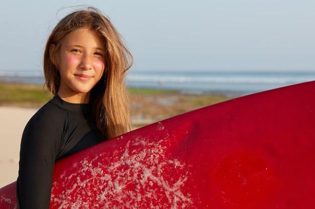 Linda adolescente com pele bronzeada saudável, usa maiô preto impermeável