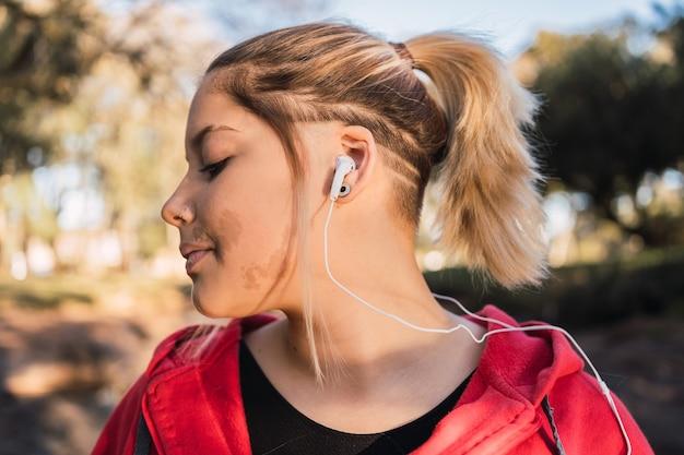 Linda adolescente com uma verruga no rosto, ouvindo música com fones de ouvido.