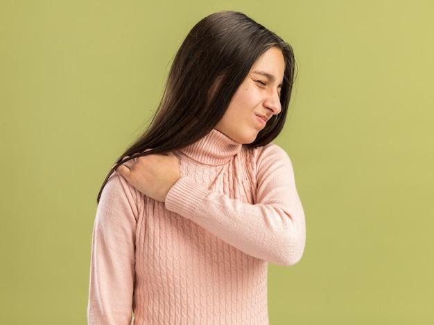 Linda adolescente dolorida em pé em vista de perfil, mantendo a mão em seu ombro com os olhos fechados, isolado na parede verde oliva com espaço de cópia