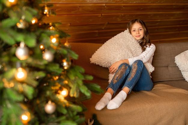 Linda adolescente em casa perto da árvore de natal