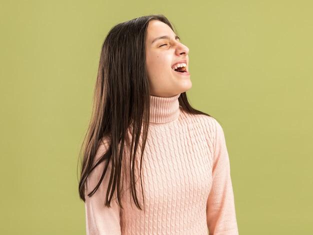 Linda adolescente sorridente em pé em vista de perfil, olhando para o lado com a boca aberta, isolada na parede verde oliva