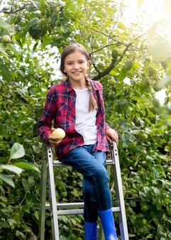 Linda adolescente sorridente sentada na escada no jardim de maçãs