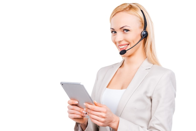 Linda ajudante. representante de atendimento ao cliente maduro e confiante trabalhando em um tablet digital e sorrindo enquanto fica de pé contra um fundo branco