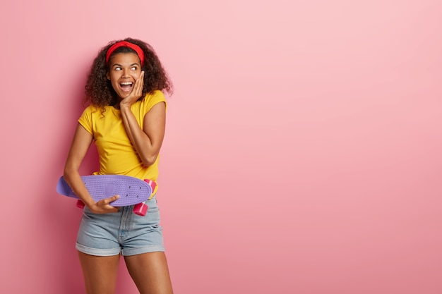 Linda alegre adolescente afro-americana tenta mostrar seu melhor no skate, segurando uma prancha roxa