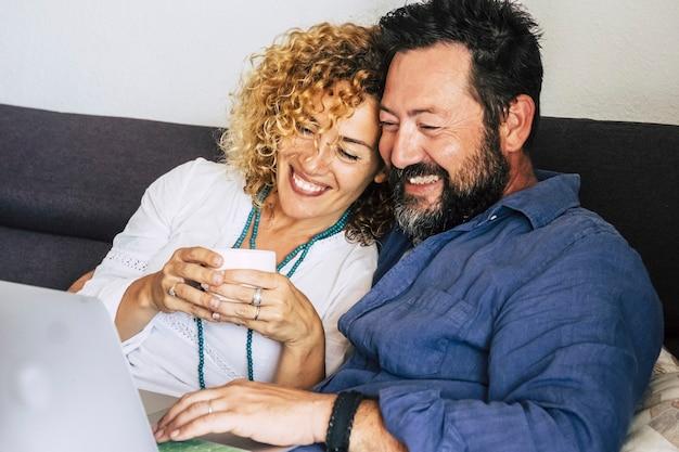 Linda alegre e feliz casal caucasiano de meia-idade em casa, sentado no sofá, usando um laptop de dispositivo de tecnologia