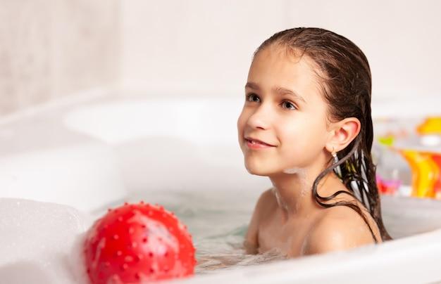 Linda alegre garotinha caucasiana tomando banho e jogando bola e anel de borracha no banheiro