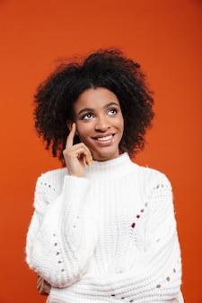 Linda alegre jovem africana vestindo uma blusa em pé sobre uma parede vermelha, olhando para longe