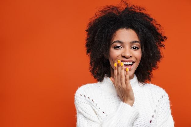 Linda alegre jovem africana vestindo uma camisola em pé sobre uma parede vermelha, rindo