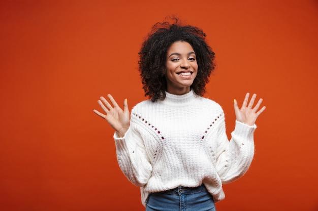Linda alegre jovem africana vestindo uma camisola em pé sobre uma parede vermelha