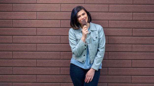 Linda alegre jovem caucasiana em uma jaqueta de couro cinza prova um sorvete de chocolate perto de uma parede de tijolos texturizados.