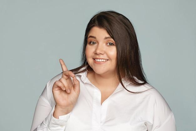 Linda alegre jovem empresária plus size de bom humor posando isolada em uma parede cinza, olhando com um sorriso feliz e confiante, mostrando algo para você, apontando o dedo indicador para o lado