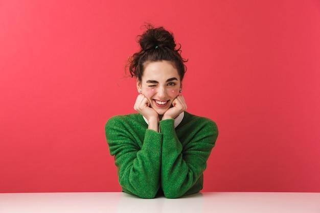 Linda alegre jovem estudante sentada à mesa isolada