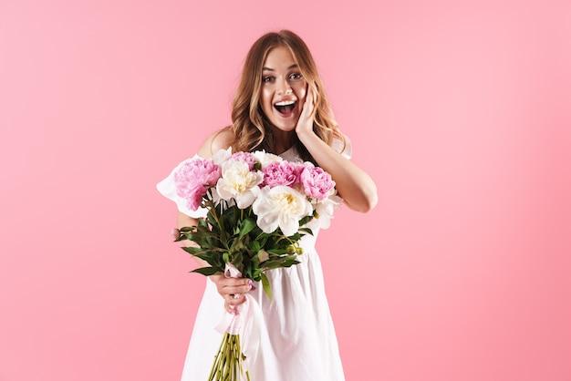Linda alegre jovem loira com um vestido de verão em pé, isolada na parede rosa, segurando um buquê de peônias
