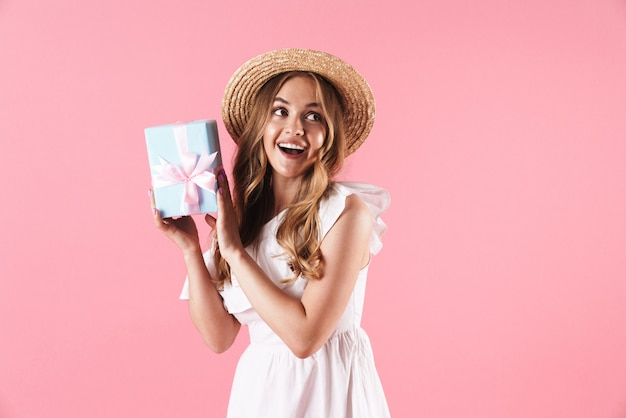 Linda alegre jovem loira com um vestido de verão em pé, isolada na parede rosa, segurando uma caixa de presente