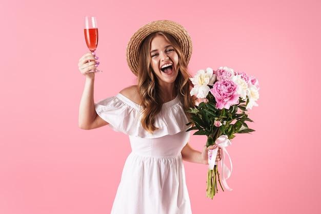Linda alegre jovem loira com vestido de verão em pé, isolada na parede rosa, comemorando com um copo de vinho e buquê de flores