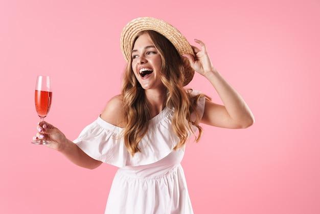 Linda alegre jovem loira com vestido de verão em pé, isolada na parede rosa, comemorando com um copo de vinho