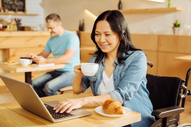 Linda alegre mulher aleijada de cabelos escuros, sentada em uma cadeira de rodas, segurando uma xícara de café, trabalhando em seu laptop e um homem sentado ao fundo