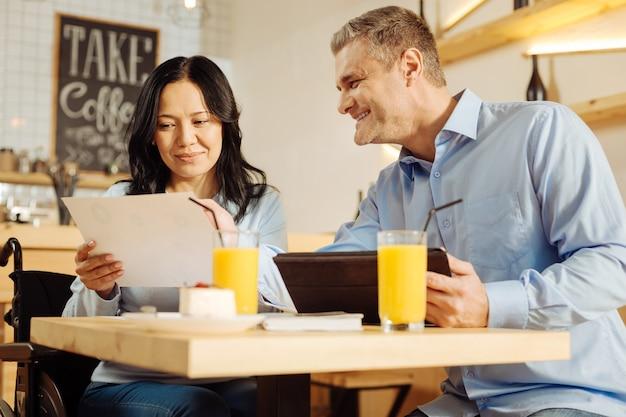 Linda alegre mulher com deficiência e um homem bonito e alegre loiro sorrindo e discutindo trabalho enquanto estão sentados em um café
