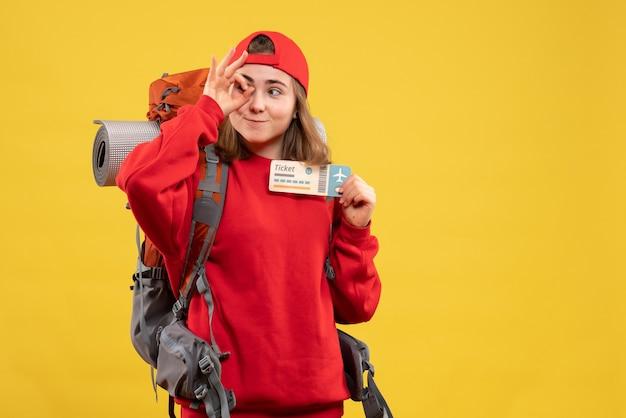 Linda alpinista com mochila segurando uma passagem de avião e gesticulando sinal de ok