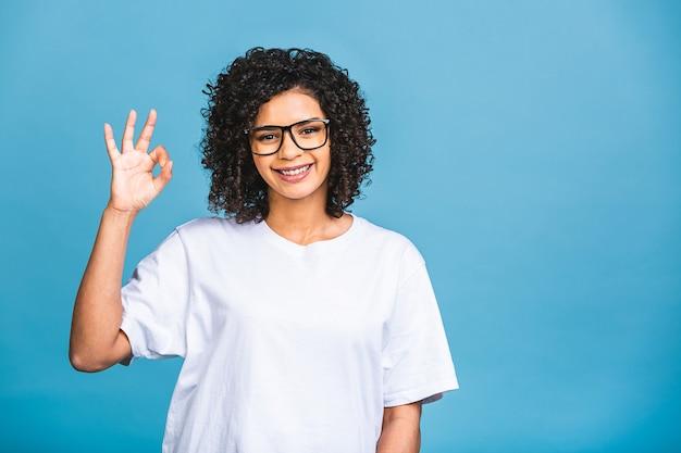 Linda aluna afro-americana com um penteado afro sorrindo isolado sobre fundo azul. ok, sinal.